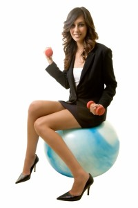 Attractive brunette smiling business woman sitting on a blue workout ball holding weights wearing black business suit on white